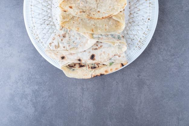 Lavash e gutab su un piatto sul tavolo di marmo.