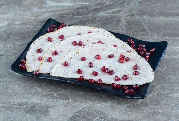 Lavash e arilli di melograno sul piatto di legno, sul tavolo di marmo.