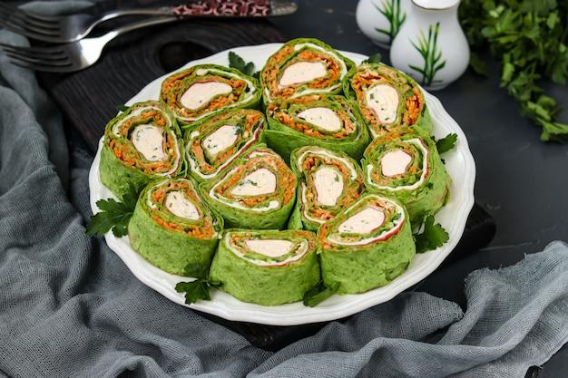 Рулет из лаваша с крабовыми палочками, шпинатом, петрушкой и морковью по-корейски на тарелке на темном фоне