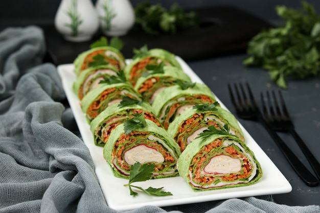 Lavash roll with crab sticks, spinach, parsley and carrots in korean style on a plate against a dark