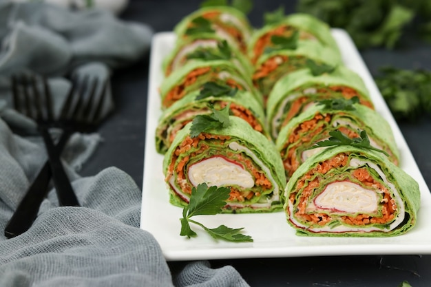Lavash roll with crab sticks, spinach, parsley, cheese and carrots in korean style on a plate against a dark background