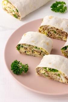 白い表面に魚、チーズ、卵、パセリを添えたラヴァッシュロール