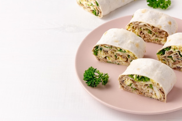 Lavash roll with fish, cheese, eggs and parsley on white surface