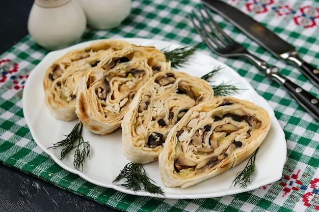 マッシュルーム、チーズ、ブラックオリーブの白いプレートにラバッシュロール、お祝いのスナック、水平方向
