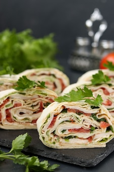 Lavash roll with smoked chicken, tomatoes, cheese and greens