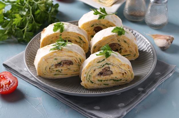 Рулет из лаваша со шпротами, сливочным сыром, огурцом и яйцом на серой тарелке на голубой поверхности