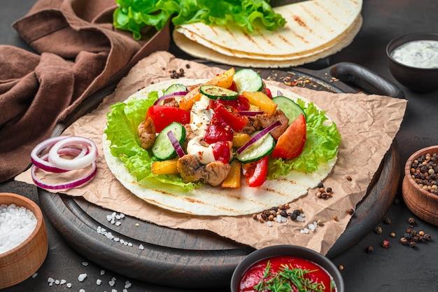 Лаваш, овощи, мясо и соусы на коричневой стене. мексиканские тако, шаурма. боковой вид крупным планом.