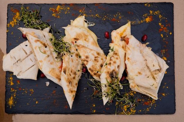 Лаваш с сыром на плоской черной тарелке, украшенной зеленью и зернами граната. ресторанное блюдо.