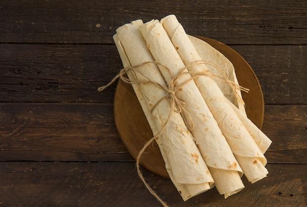 アルメニアの平らなパンlavash。木製のまな板にピタパン。コピースペース。