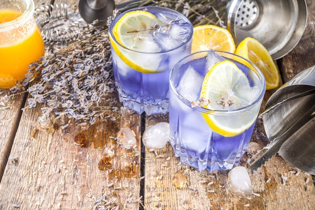 Lavender alcoholic cocktail, lavandula lemonade with lemon and honey, on wooden background with lavender bunch and barmen utencils, copy space