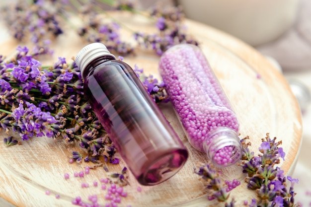 Lavender bath cosmetics products in bottles on white wooden rustic board, fresh lavender flowers, soap, bath beads. lavender essential oil, natural spa products. aromatherapy treatment.