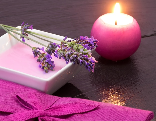Lavender bath foam with scented candle and flowers