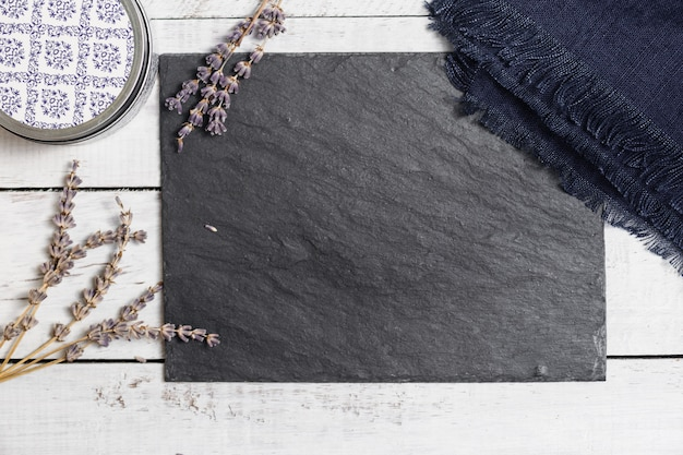 Lavender on black graphite board upon white rustic wooden table.