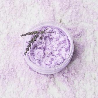 Lavender body scrub in a bowl on a bath salt background. spa concept.