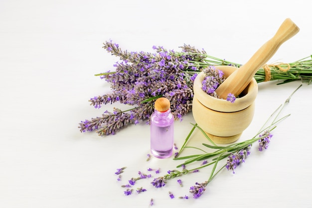 Букет лаванды и цветы лаванды в деревянной ступке с пестиком и маслом лаванды. ароматный, здоровый образ жизни.