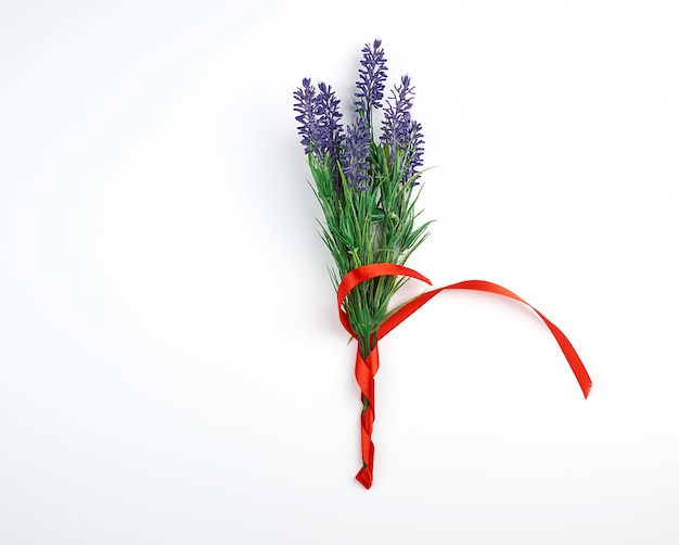 Lavender bouquet and red ribbon on a white background, top view