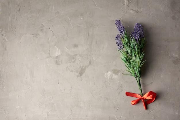 Ветвь лаванды и текстура серой цементной стены с шишками шпателя, полный кадр, крупный план