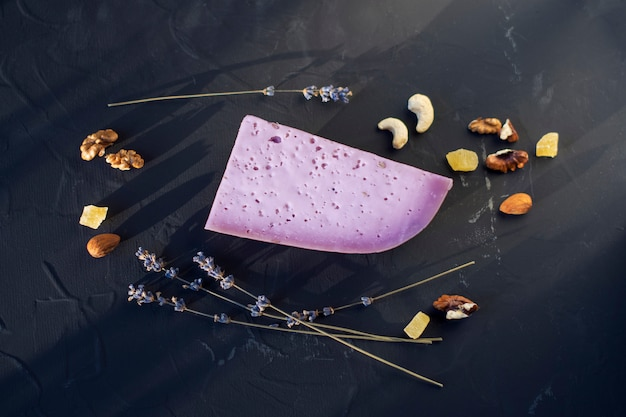 Lavender cheese with nuts on a black board
