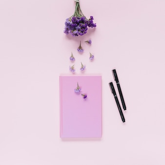 Lavender over the closed notebook and two felt-tip pens on pink background