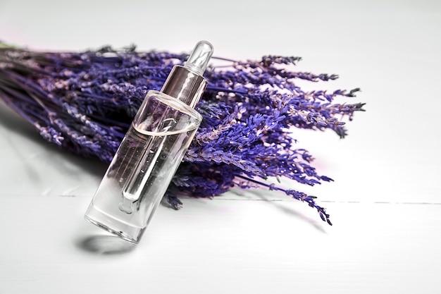 ガラスのpepitと木製のテーブルの上の乾燥したラベンダーの花とスポイトボトルのラベンダー化粧品オイル