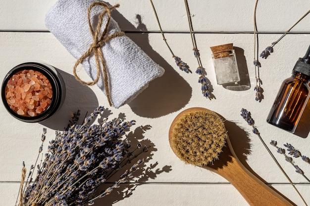 ラベンダー化粧品-マッサージブラッシュ、海塩、タオルを含む天然ラベンダーエッセンシャルオイル。アロマテラピー、スパ、ウェルネスの背景。白いテーブルの上面図。