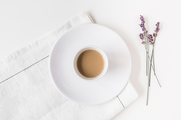 Lavender and cup of coffee on napkin over white backdrop