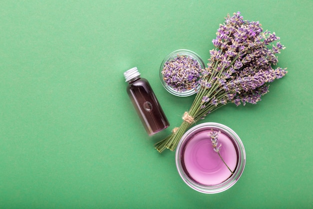 Lavender essential oil bottle on green color background fresh lavender flowers aromatherapy
