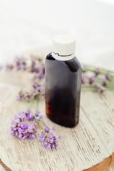 新鮮なラベンダーの花と白い木製の素朴なボード上のラベンダーエッセンシャルオイルボトル。アロマテラピートリートメント、天然オーガニックスパ化粧品、ホメオパシー薬剤師ラベンダーハーブ。