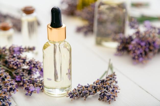 白い木製の素朴なテーブルの新鮮なラベンダーの花にラベンダーエッセンシャルオイルガラス瓶血清スポイト。アロマテラピートリートメント、ナチュラルスパコスメティックス、薬剤師ラベンダーハーブ。スキンケアヘア化粧品。