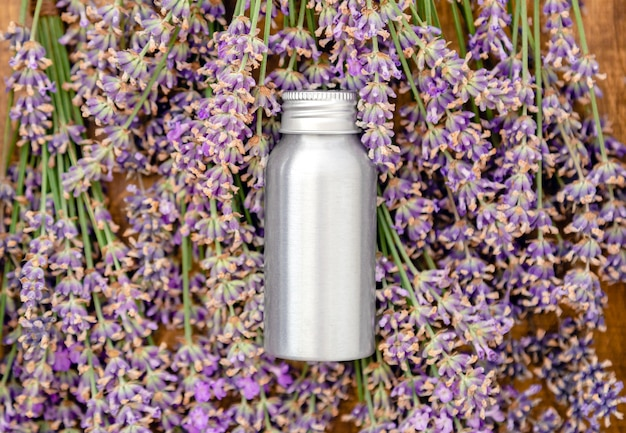 Lavender essential oil metal silver bottle on fresh lavender flowers. flat lay apothecary herbs for aromatherapy treatment. lavender skincare cosmetic. natural spa beauty products.
