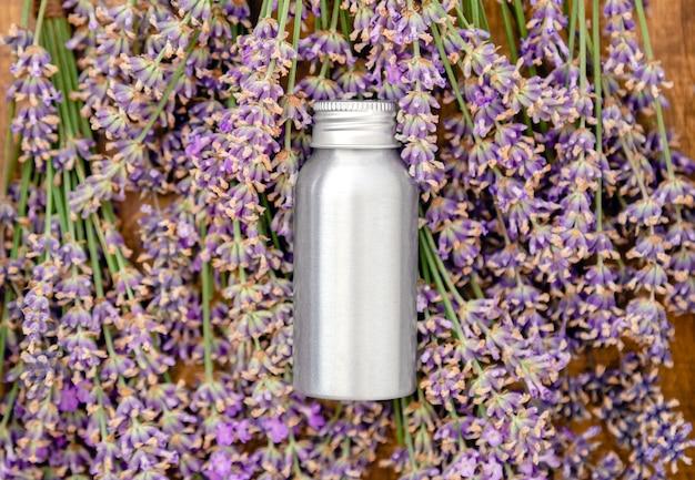 新鮮なラベンダーの花にラベンダーエッセンシャルオイルメタルシルバーボトル。アロマテラピー治療のためのフラットレイアポセカリーハーブ。ラベンダースキンケア化粧品。ナチュラルスパ美容製品。