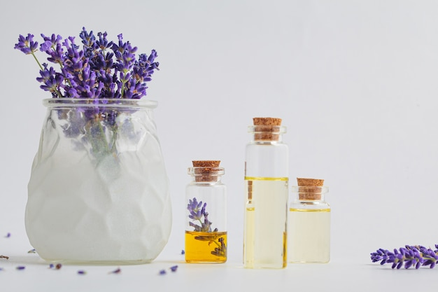 Lavender essential oil in small glass bottles and lavender flowers in a mortar, white background.