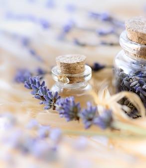 유리병에 물방울이 있는 라벤더 에센셜 오일과 말린 라벤더 꽃. 얕은 dof와 선택적 초점입니다.