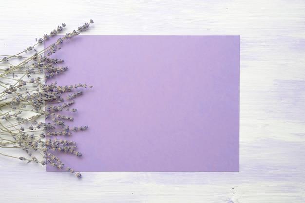 Цветок лаванды над фиолетовым фоном против деревянной текстуры