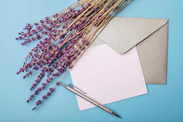 라벤더 꽃과 파란색 배경에 봉투와 빈 종이. 위에서 봅니다. 조롱하다