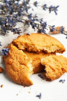 白いテーブルの上のラベンダーの花とクッキー