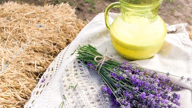 プロヴァンスの畑の干し草の山に横たわるラベンダーの花とミルクの瓶。