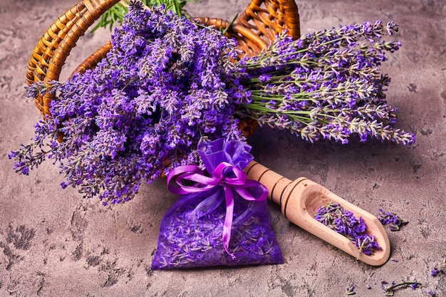 Lavender flowers in basket and aromatic bag on gray concrete background. top view.