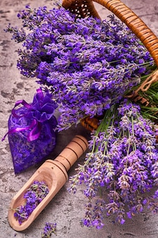 Lavender flowers in basket and aromatic bag on gray concrete. top view.