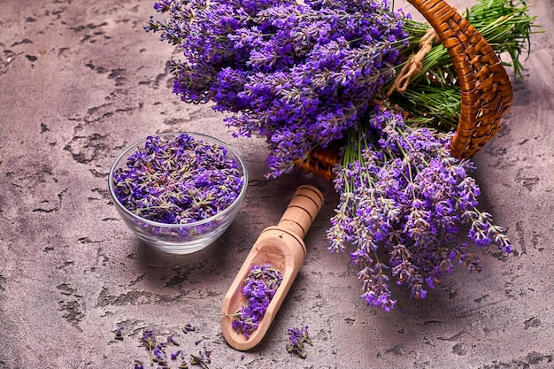 Lavender flowers in basket on gray concrete background. top view.