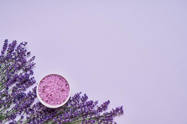 Lavender flowers and bath salt in bowl on lilac backdrop