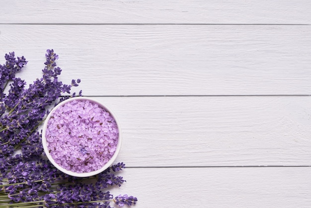 Lavender flowers and bath salt in bowl on white wooden