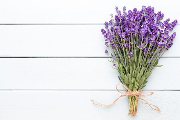 ラベンダー色の花、素朴なテーブルの上に花束。