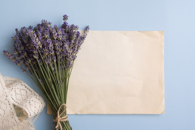 Lavender flowers in a bouquet on the table near a blank sheet old paper for text.