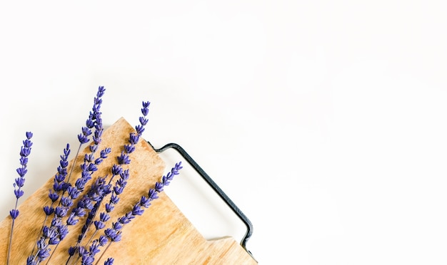 Lavender flowers branches on a wooden board with space for text. top view, flat lay, copy space.