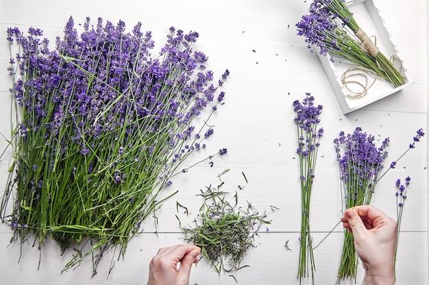 흰색 나무 테이블 평면 누워 여성 손에 신선한 꽃다발을 만들기위한 라벤더 꽃