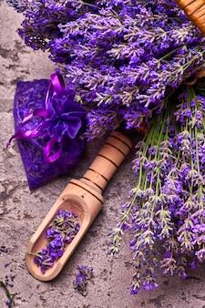 바구니와 회색 콘크리트 배경에 향기로운 가방에 라벤더 꽃. 평면도.