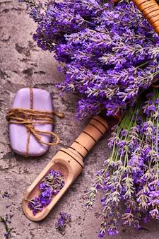 バスケットのラベンダーの花と灰色のコンクリートの背景に芳香族石鹸。上面図。