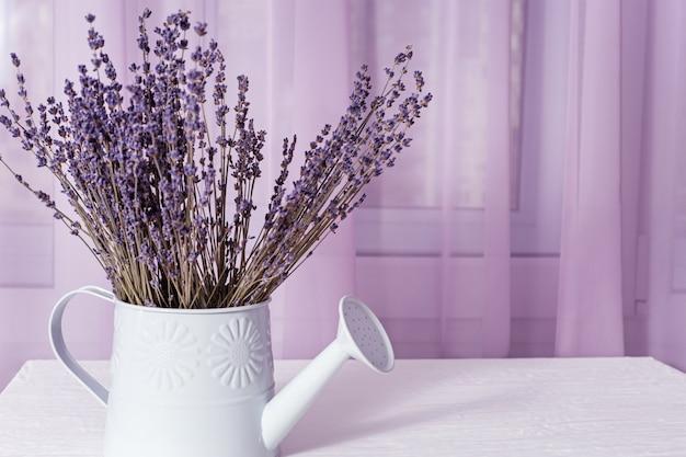 水まき缶でラベンダー色の花がチュールの布でウィンドウにコピースペース。ソフトフォーカス。