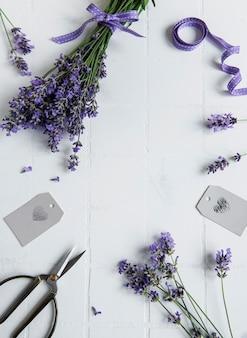 흰색 타일 배경에 라벤더 꽃, 가위, 리본